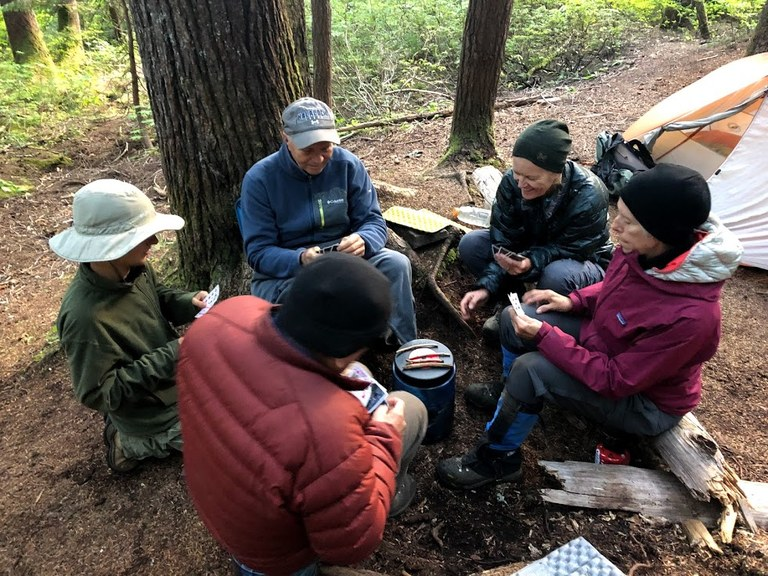 Volunteers play cards at camp after a long day of trail work. Photo by Emily Snyder.