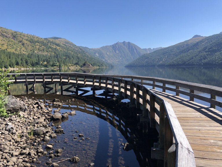 A wooden boardwalk curves out over a section of lake and returns to land on the other side. Photo by Jennekehikes