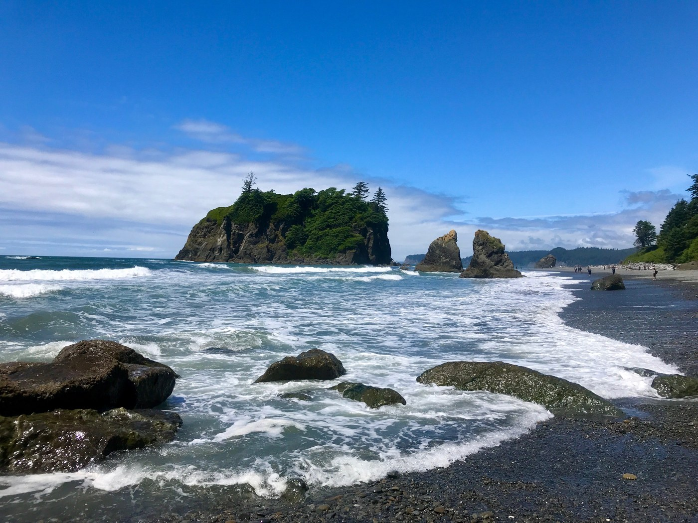 A stretch of beach with small waves crashing and a big haystack rock in the distance. Photo by egorup04.