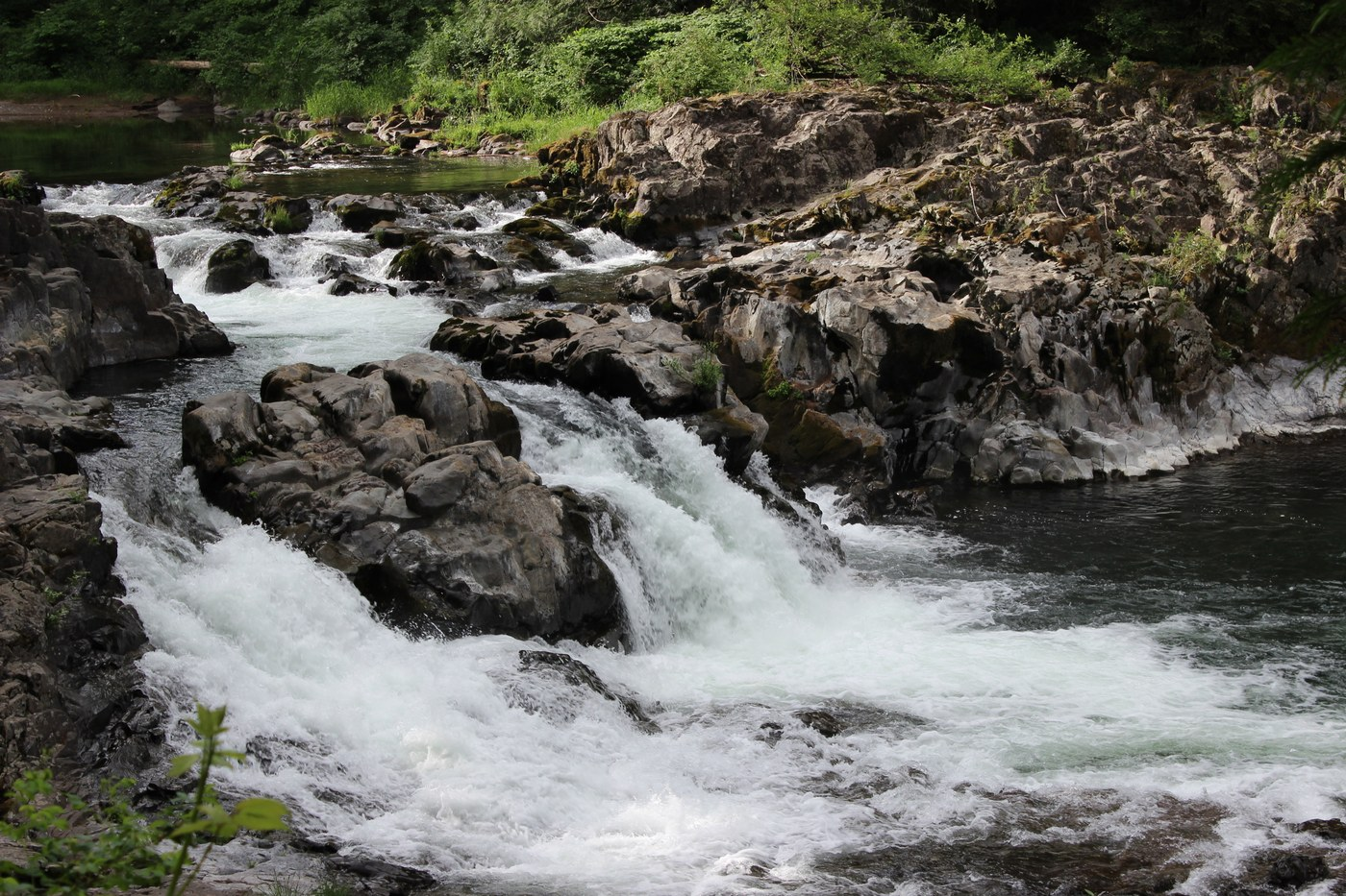 A wide short waterfall flowing over rocks. Photo by Tyaira36.