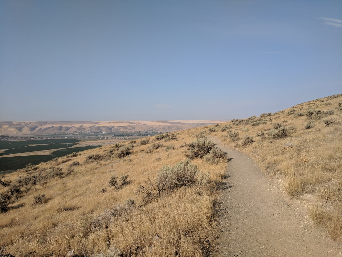 Badger Trail along dry grassy hills with a view to a distant town in the valley. Photo by Luffles.
