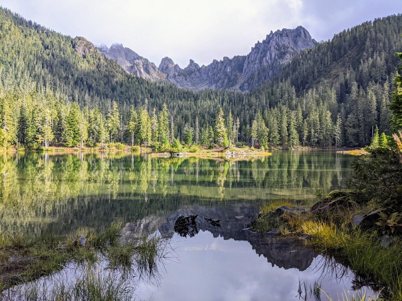 A aquamarine lake ringed by trees and rocks.