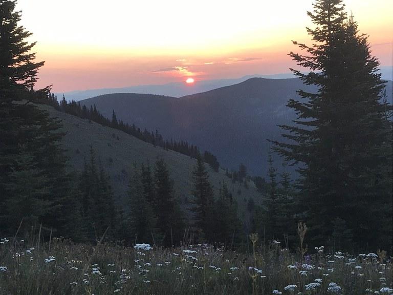 Sun setting behind a ridge of mountains.