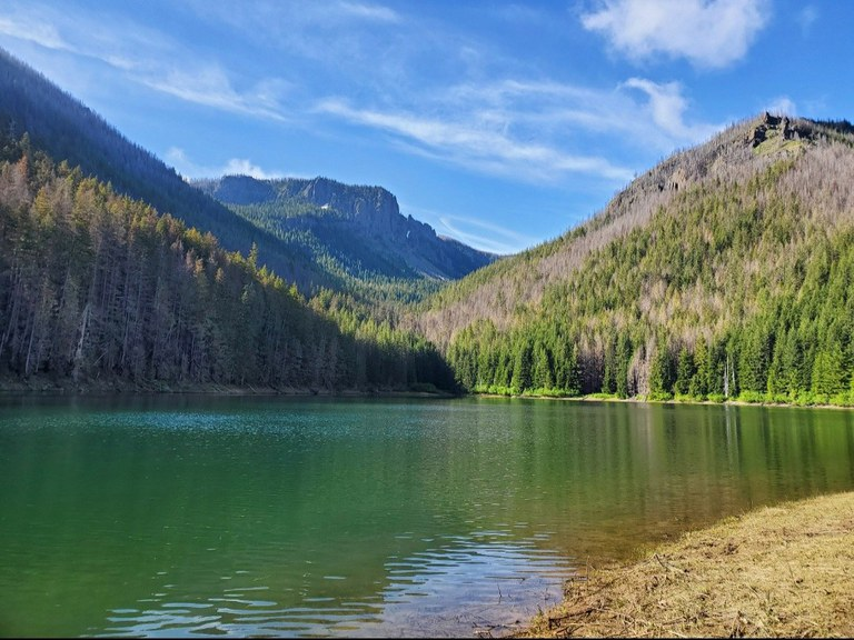 An aquamarine lake surrounded by forest and a rocky outcropping in the distance. Photo by KZMoves.
