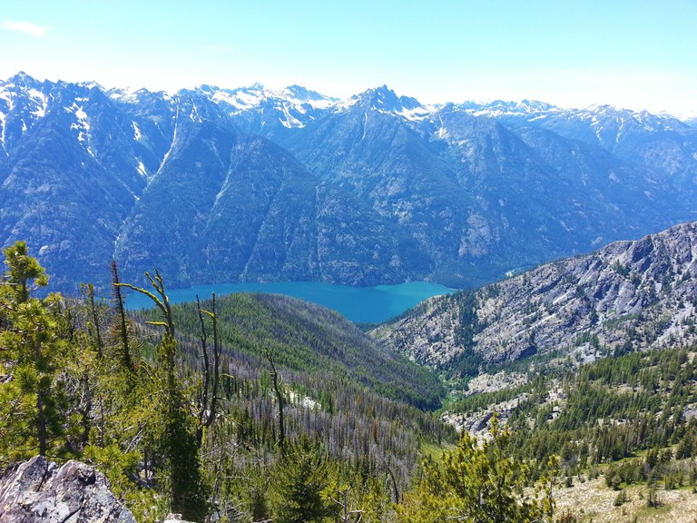 View from a high ridge looking down at Lake Chelan and across to a ridge of mountains rising from the lakeshore. Photo by Karmot