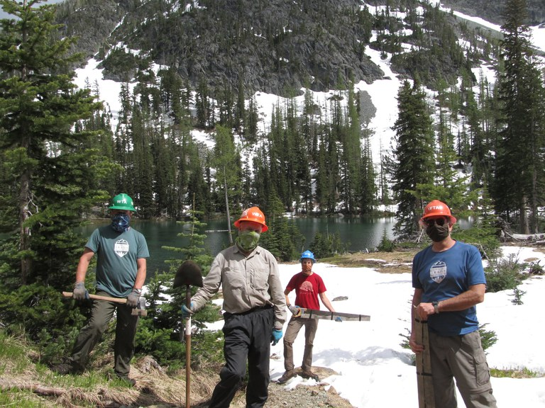 Several volunteers pose for the camera holding their trail tools. Photo by Jim Langdon.