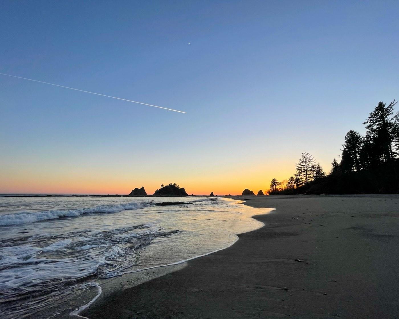 A sun sets beyond a sandy beach, casting warm colors into the sky.