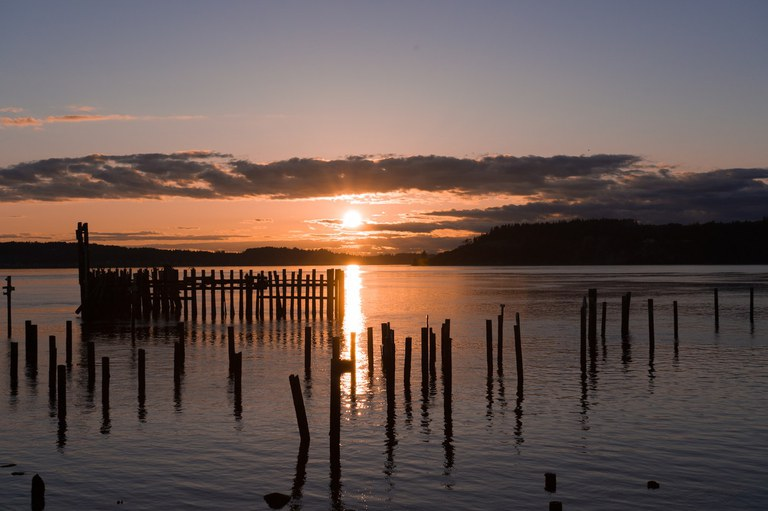 Old wooden piers sticking out of the water with the sunset in the background.