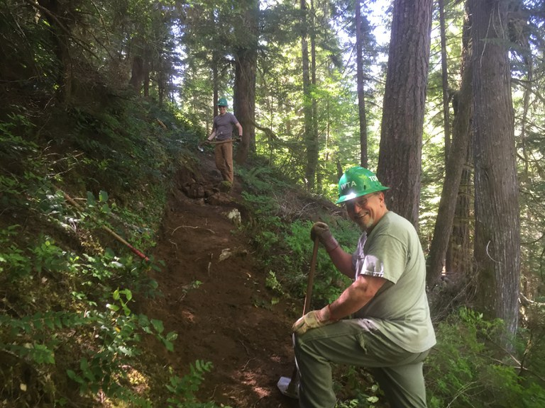 Two volunteers with shovels work on the trail tread. WTA Archive.