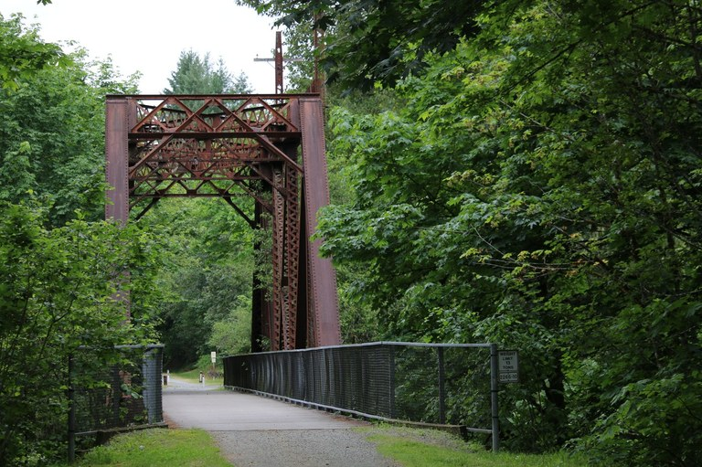 The paved surface of the Cedar River Trail leads to a rusty bridge over the Cedar River.