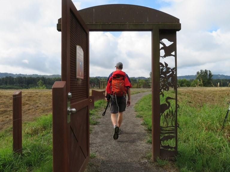 A man walks through a metal arch to enter an open grass field.
