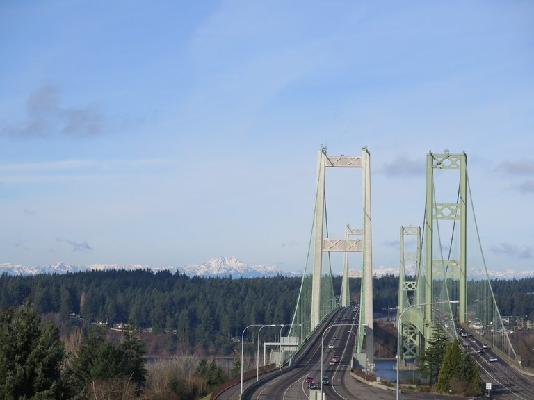 View west across the Tacoma Narrows Bridge with the Olympics peaking out. Photo by Erik Morgenstern.