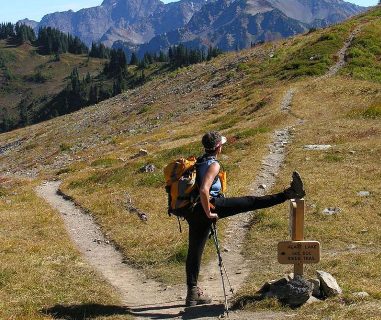 Hiker Sherri Cassutto takes a stretching break on the High Divide Trail in the Olympics. By working on strenght, endurance, flexiblity and balance, you'll make your time on trail more enjoyable.