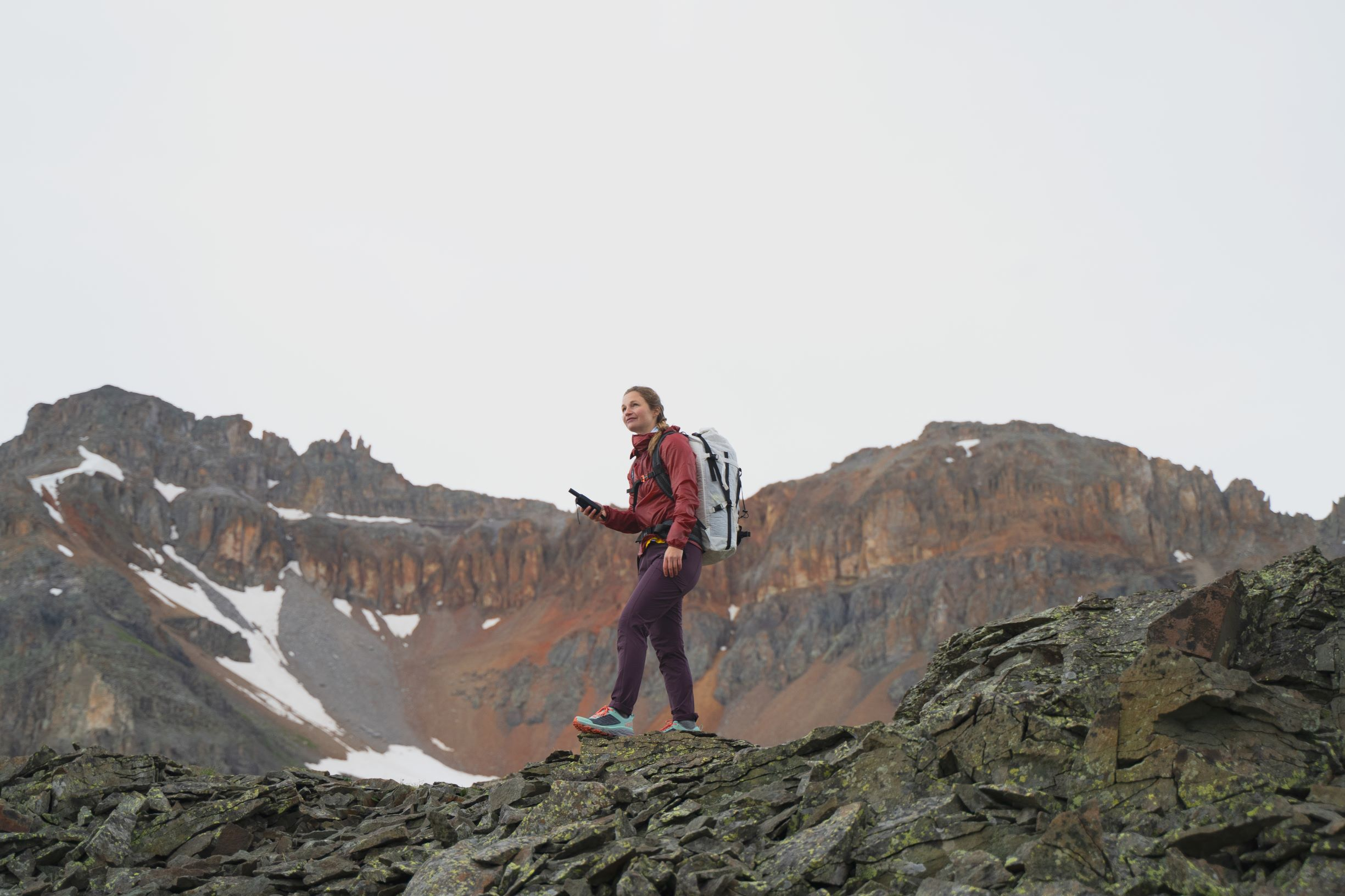A hiker stands calmly holding a SPOT device in their hand and overlooking a rocky hillside.
