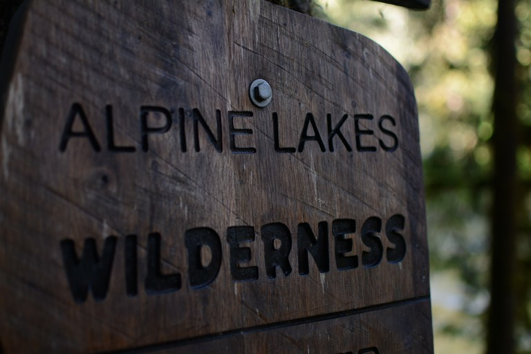 A wooden sign that says Alpine Lakes Wilderness.