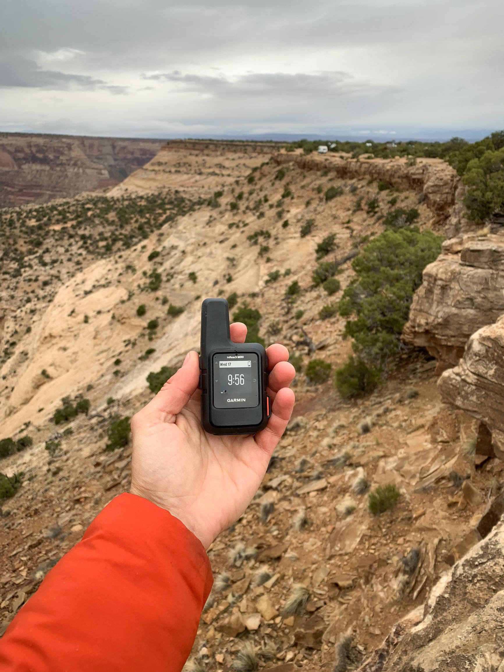 An outstretched arm holds a small Garmin device in their palm, with a scenic desert expanse beyond them.