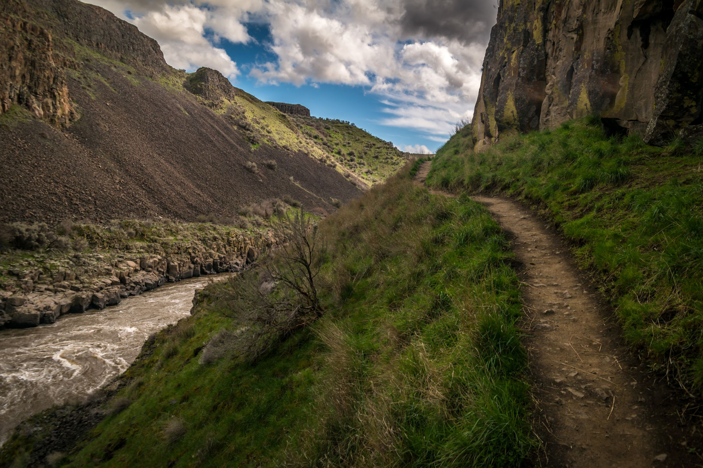 A dirt trail wins through a canyon with a river rushing below to the left, and a steep rocky wall rising above it to the right.