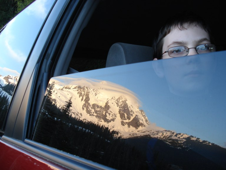 A passenger looks at a mountian through a car window. Photo by Michelle Gephart.