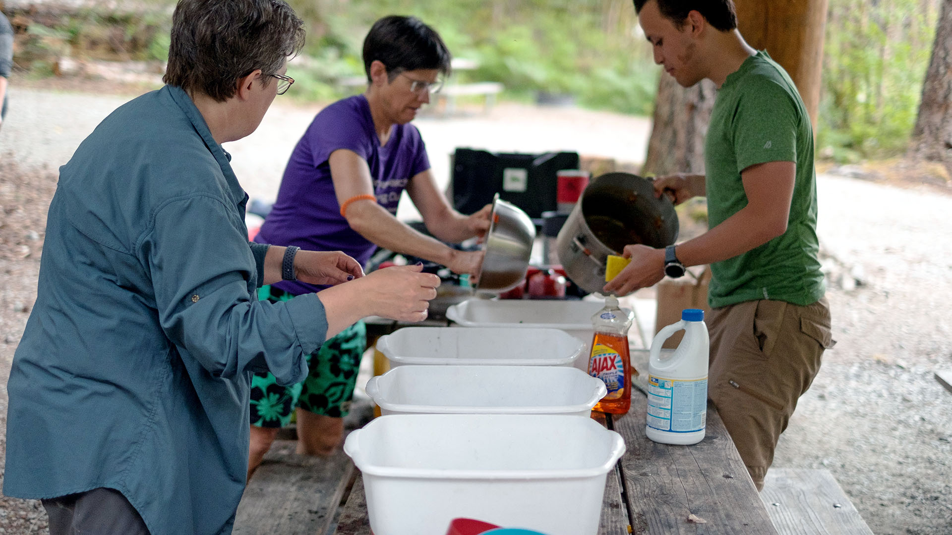 Campers wash dishes in plastic bins