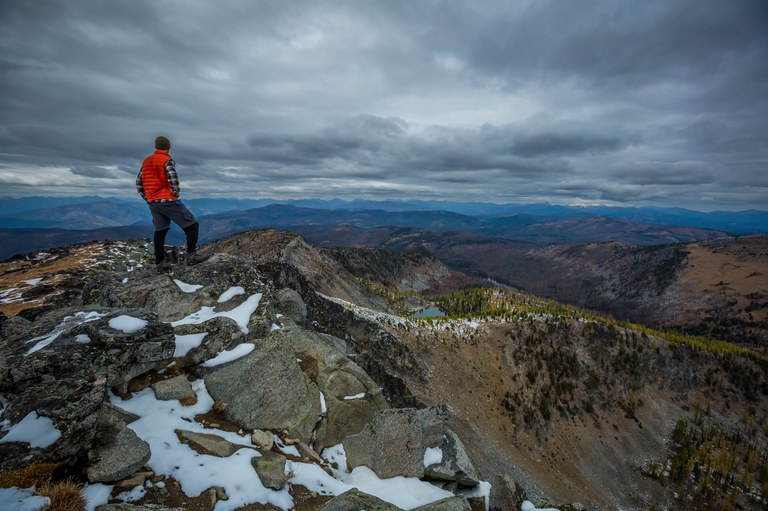 A hiker in an orange vest stands on a peak