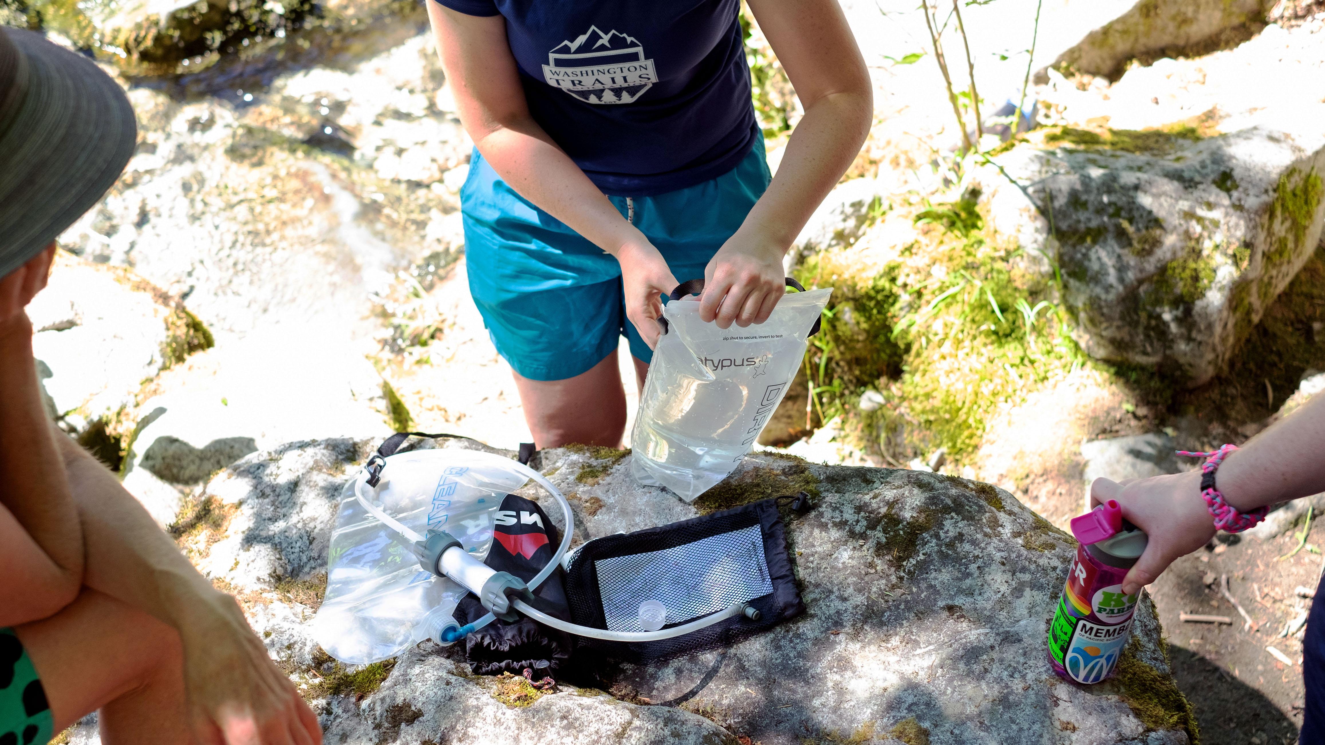 A camper assembles a gravity water filter