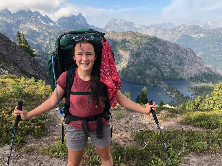A hiker posing with trekking poles along the PCT.