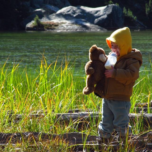 Kid at lake with teddy bear wade johnson