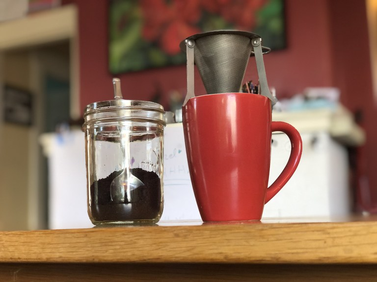 A mug with a small, backpacking drip coffee filter hovering over it.