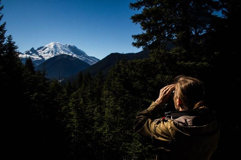 A hiker looking through binoculars.