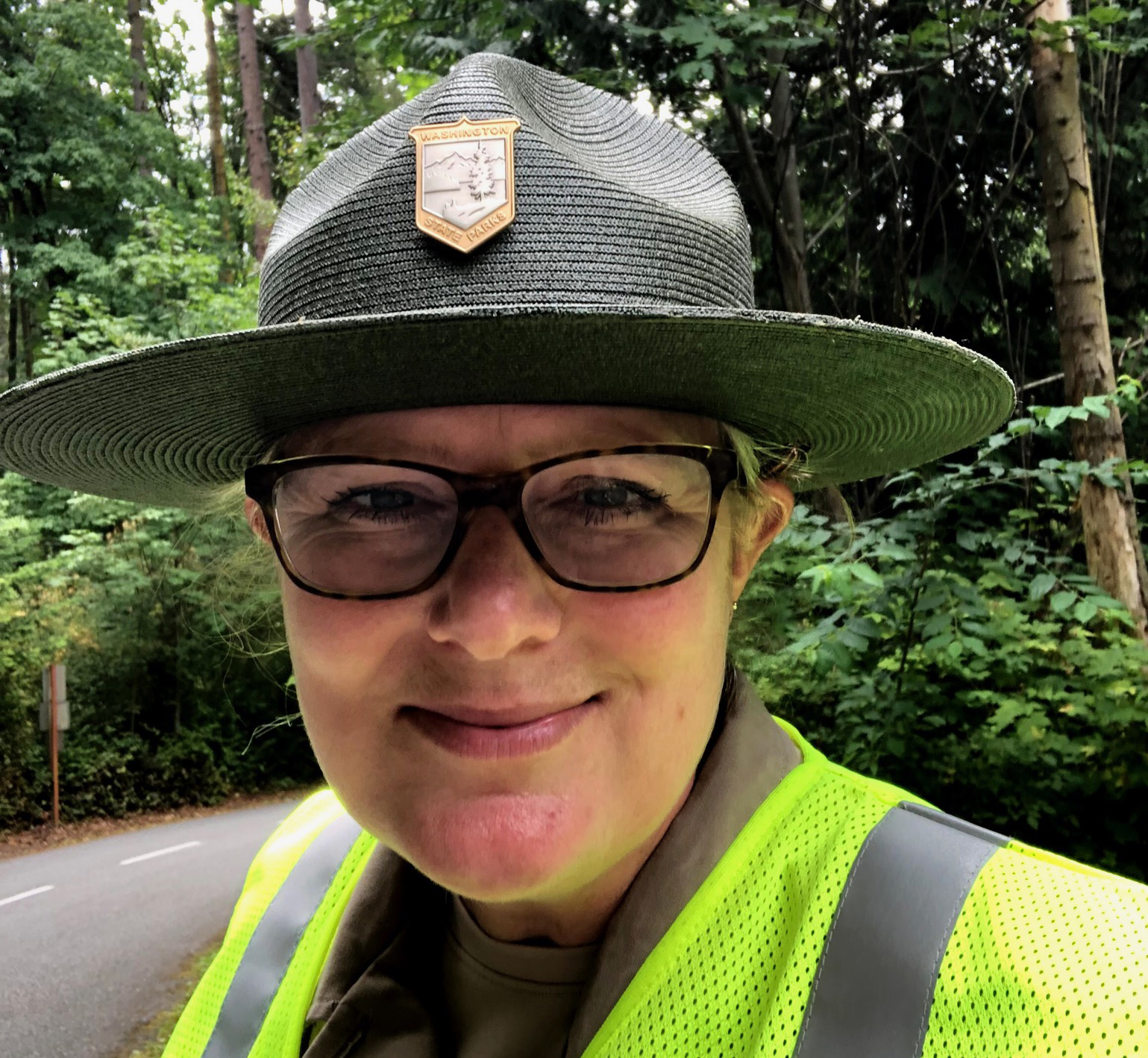 Amber wears her uniform, including a flat brimmed hat and colorful safety vest.
