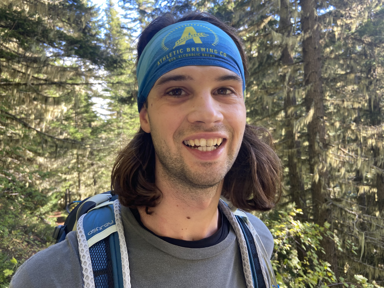 """A hiker wearing a backpack and blue headband saying """"Athletic Brewing"""" smiles at the camera, with evergreen trees in the background."""