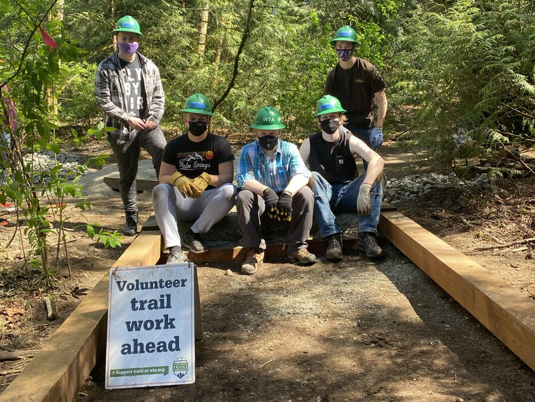Five volunteers, wearing WTA green hard hats, sit and stand amid a partially finished structure to lift the trail out of a wet area.