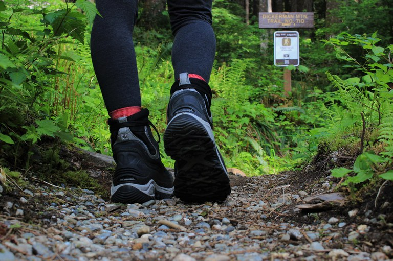 A hiker wearing black boots walks up a dirt trail with a sign for Mount Dickerman in the background.