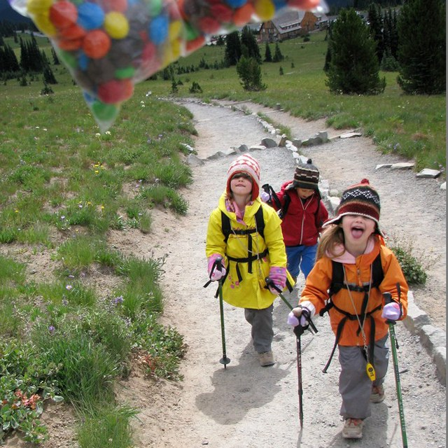 A group of kids looks at a brightly colored bag of candy.