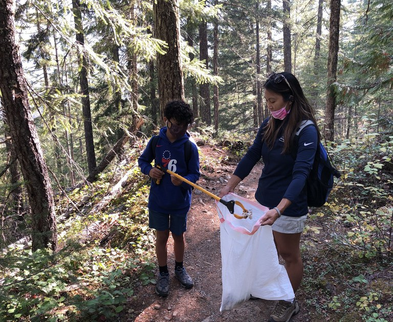 Hikers picking up trash on trail. Photo by Sandy Yee