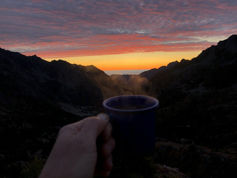 A cup of coffee held up to a sunset.