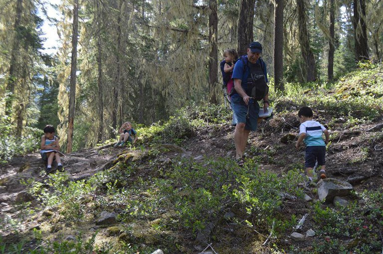 A man wearing a child in a backpack leans down toward another child walking toward him. Two kids are in the background. They are all in a forest area.