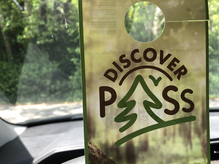 A photo of a Discover Pass with greenery in the background.