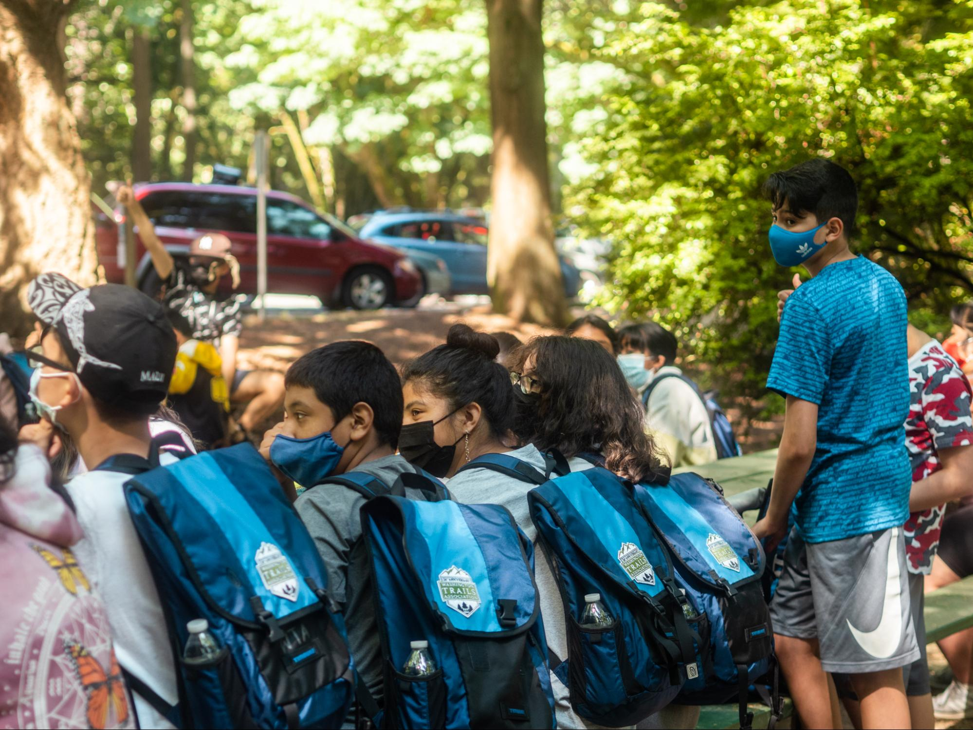 A group of kids wearing masks and blue WTA backpacks wait to head out on a hike.