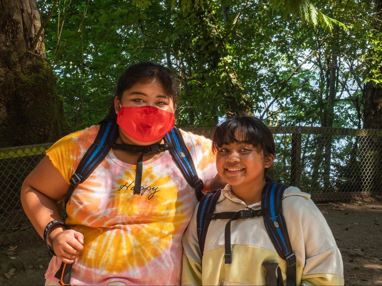 Two students, both wearing backpacks, stand in front of trees and a small fence and smile at the camera.