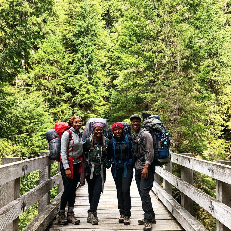 Four hikers standing together on a bridge and smiling. All are wearing backpacking packs.