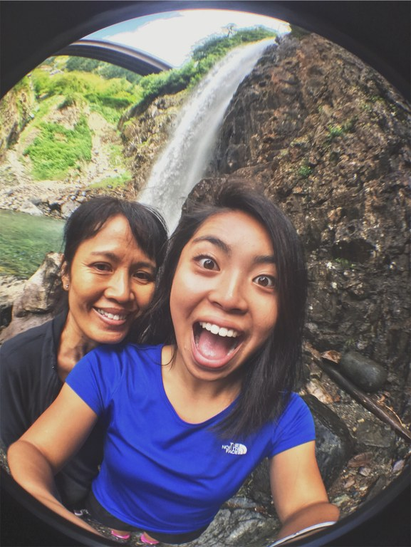 Two people with bright smiles pose for a selfie with a waterfall behind them.