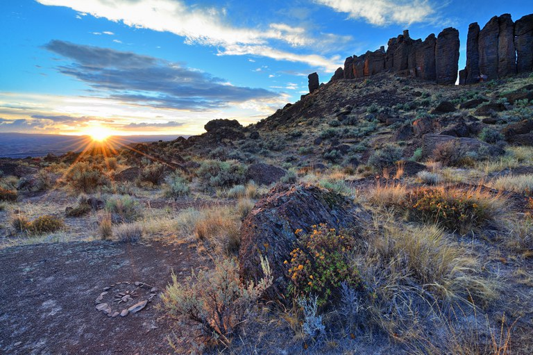 Columns of dark basalt rise in the back of the photo with sagebrush in the front as the sun sets.