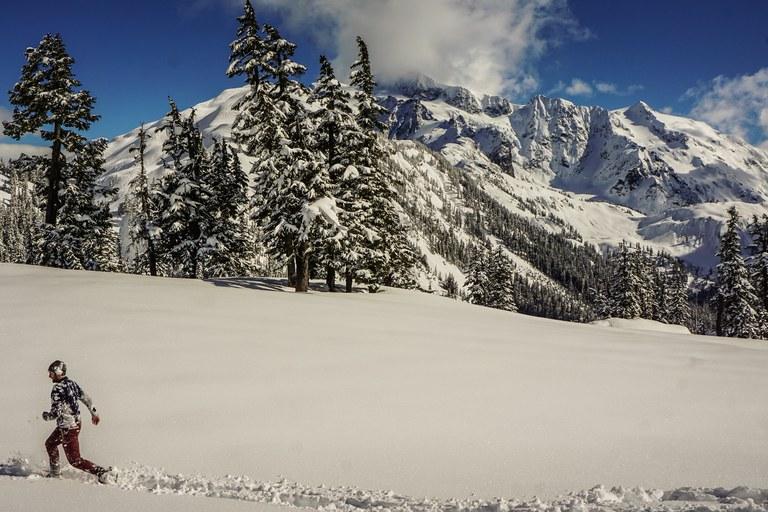 A man runs across a snow landscape. Photo by Mathew Leaman.