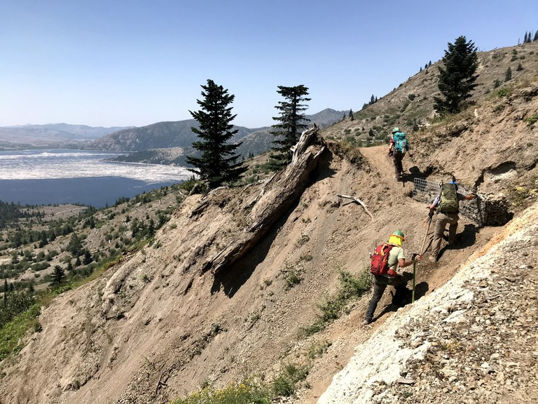 Trail workers hiking up to work on the gabion along Independence Pass.