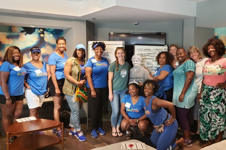 A group poses after a discussion about getting outside with Girl Trek.