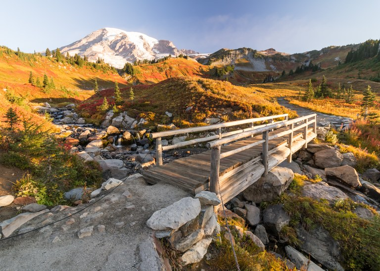 A wooden bridge spans a creek through a golden meadow with Mount Rainier in the distance. Photo by Muhamad Said.