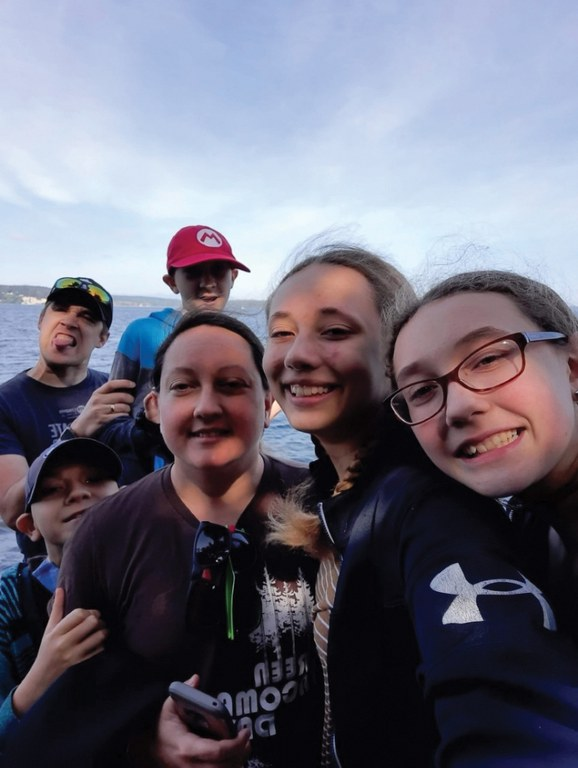 A family of six smiles for a selfie with blue water and blue sky in the background.