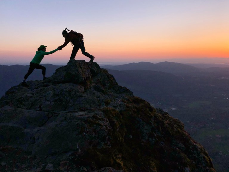 A hiker holds out there hand to help another hiker step up onto a rock promontory.