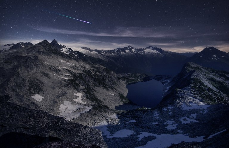 A meteor streaks across the sky over mountains and a lake.
